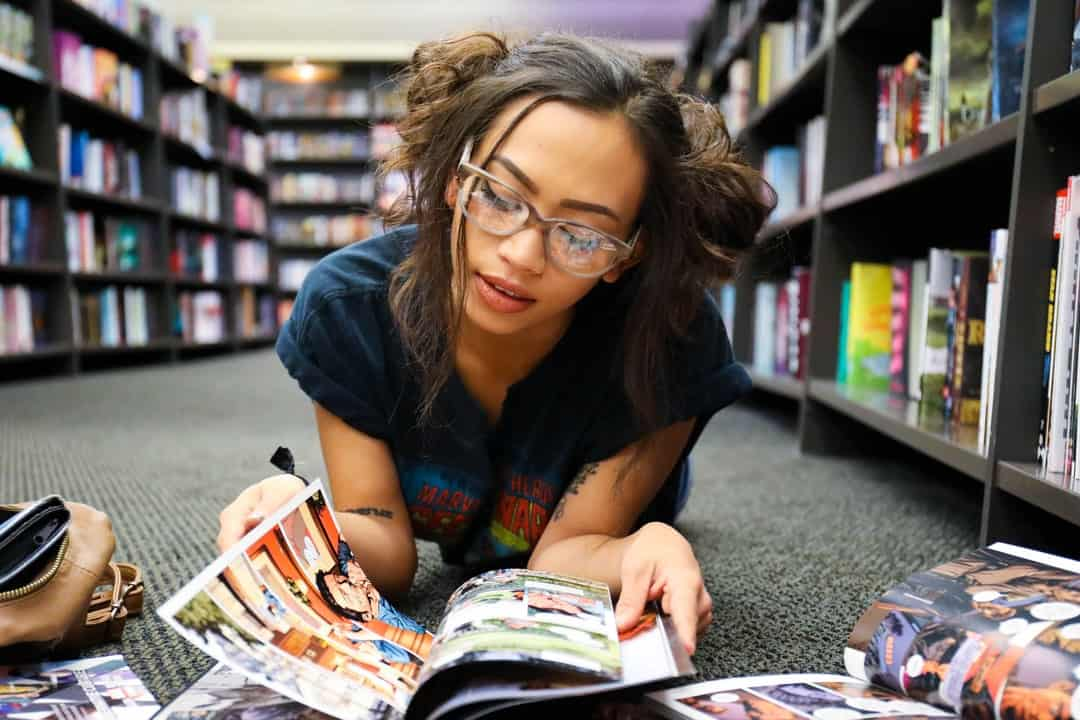 A woman sitting at a table looking at a book shelf